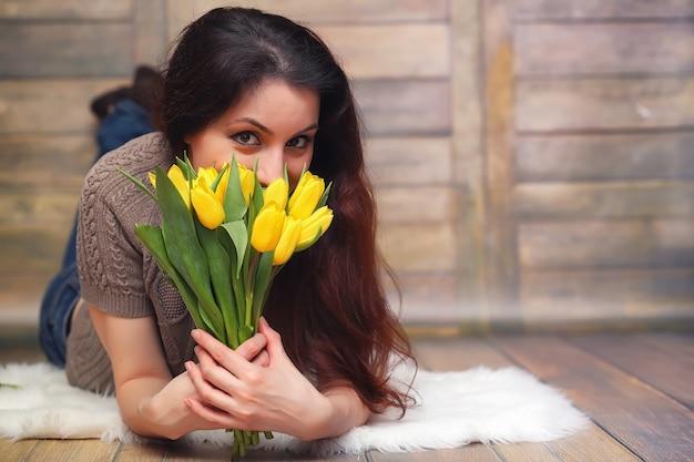 Dziewczyna z bukietem żółtych tulipanów. dziewczyna z prezentem kwiatów w wazonie. prezent dla dziewcząt na kobiece wakacje z żółtymi tulipanami na podłodze.