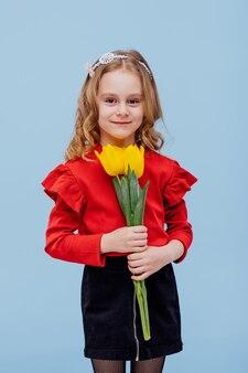 Dziewczyna z bukietem żółtych tulipanów ubrana na czerwono, odizolowana na niebiesko