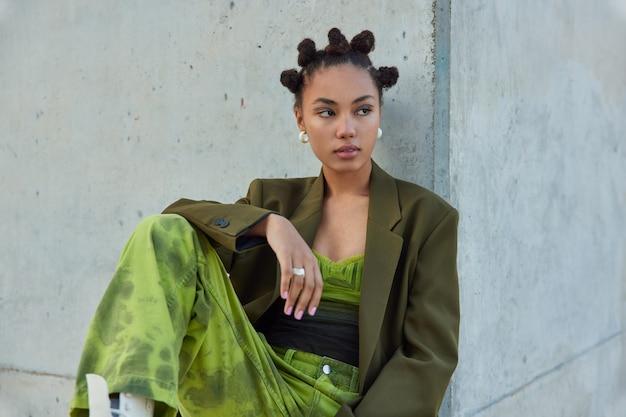 Dziewczyna z bułkami fryzura żywy makijaż ubrana w zieloną kurtkę i dżinsy pozuje przed szarą ścianą odwraca wzrok głęboko zamyślona odpoczywa po spacerze poza miastem karczmy