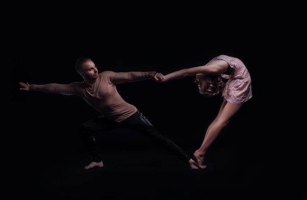Dziewczyna z chłopakiem wykonują piękne elementy gimnastyczne. piękna para akrobatyczna. czarne tło