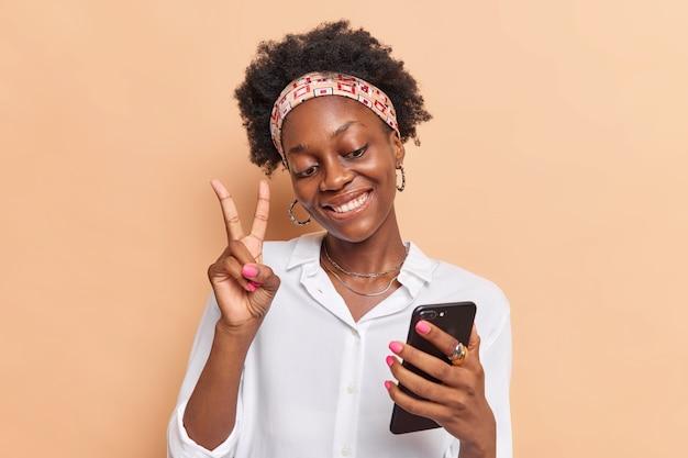 Dziewczyna z ciemną skórą, kręconymi włosami afro sprawia, że gest pokoju robi selfie lub prowadzi wideorozmowę przez smartfon, nosi białą koszulę z opaską na głowie na białym tle na beżowym bacground. koncepcja technologii