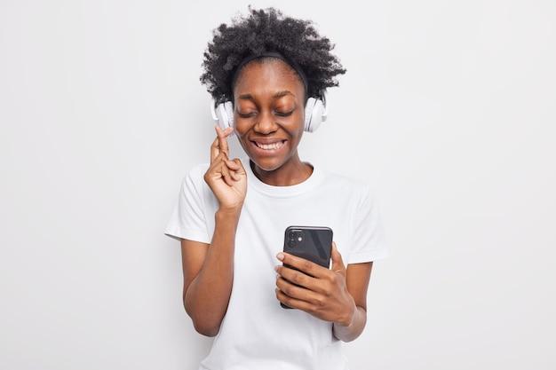 Dziewczyna z ciemnymi włosami trzyma skrzyżowane palce wierzy w szczęście trzyma nowoczesny telefon słucha muzyki przez słuchawki pobiera piosenkę do playlisty ubrana swobodnie na białej ścianie
