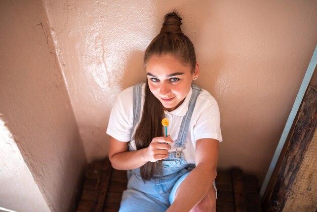 Dziewczyna z cukierkiem na patyku w zrujnowanym domu. wysokiej jakości zdjęcie