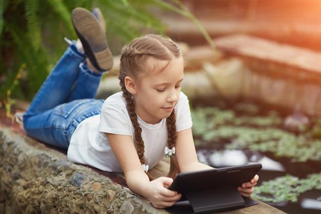 Dziewczyna z cyfrową pastylką w ogródzie botanicznym