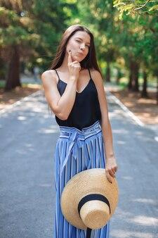 Dziewczyna z czapką w dłoniach idzie przez park, pokazuje dłoń na policzku. sumienie. czysta skóra.