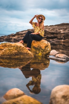 Dziewczyna z czarnymi spodenkami i słomkowym kapeluszem w naturalnym krajobrazie nad morzem o zachodzie słońca