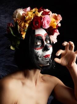 Dziewczyna z czarnymi włosami jest ubrana w wieniec z różnokolorowych róż, a na jej twarzy wykonany jest makijaż cukrowa czaszka do dnia zmarłych
