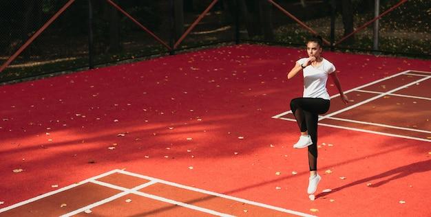 Dziewczyna z czarnymi włosami, trenująca sama na stadionie