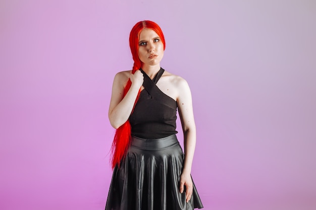 Dziewczyna z czerwonymi długimi włosami i skórzaną spódnicą pozuje na różowym tle