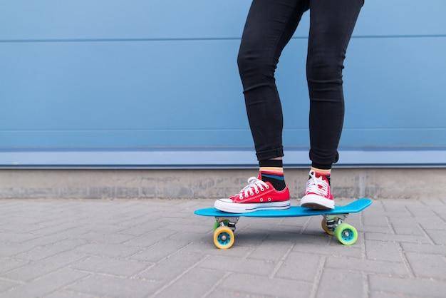 Dziewczyna z czerwonymi facetami jedzie na błękitnej deskorolce na powierzchni niebieskiej ściany