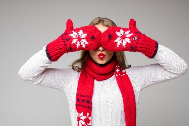 Dziewczyna z czerwonymi nadąsanymi ustami w białym swetrze i czerwonym szalikiem wokół szyi, ukrywając oczy za rękawiczkami z zimowym świątecznym wzorem.