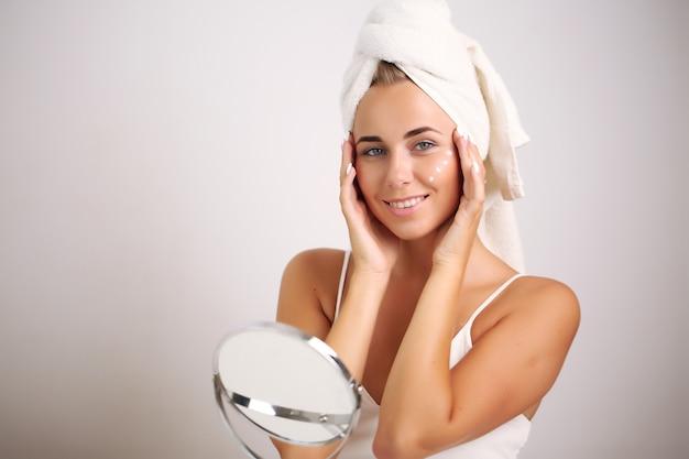 Dziewczyna z czystą, świeżą skórą dotykającą własnej twarzy