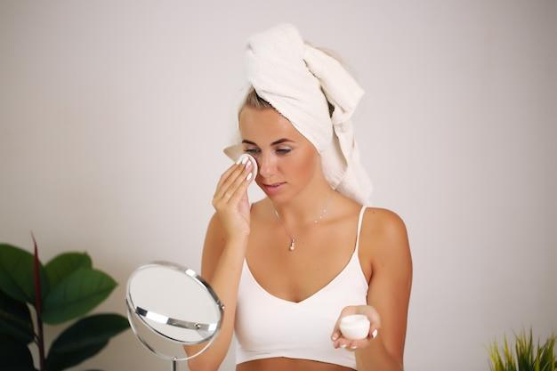 Dziewczyna z czystą, świeżą skórą dotykającą własnej twarzy.