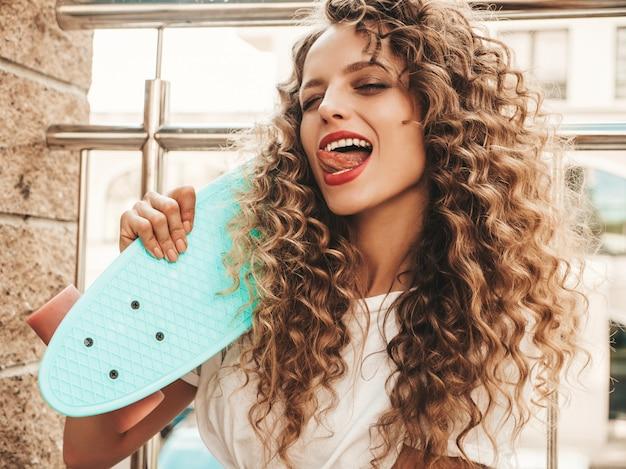 Dziewczyna z deskorolka niebieski grosz pozowanie na ulicy wyświetlono język