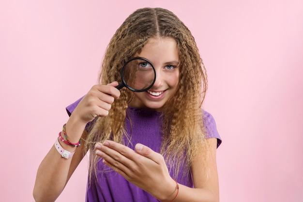 Dziewczyna z długimi blond włosami kręconymi patrząc przez szkło powiększające