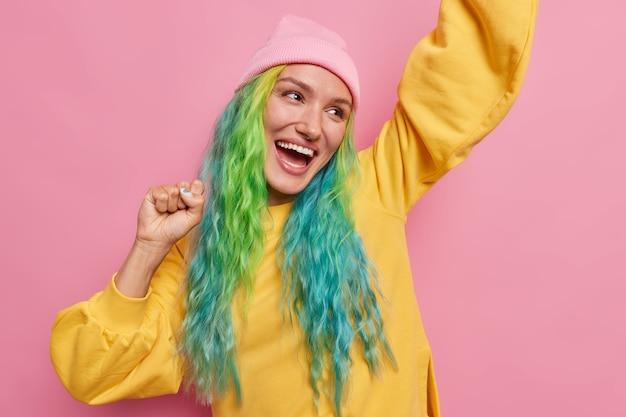 Dziewczyna z długimi farbowanymi włosami sprawia, że mistrz tańczy, podnosi ręce do góry, wygląda szczęśliwie, jakby zwycięzca nosi kapelusz i żółty sweter na różowym tle
