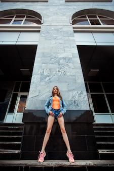 Dziewczyna Z Długimi Nogami W Szortach I Pomarańczowej Bluzce Premium Zdjęcia