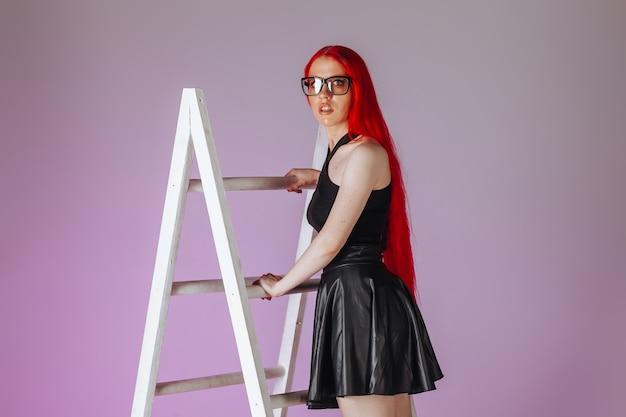 Dziewczyna z długimi rudymi włosami w okularach i skórzanej spódnicy wspina się po drabinie na różowym tle