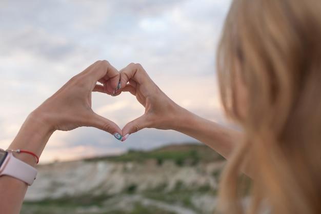 Dziewczyna z długimi włosami co symbol serca rękami.