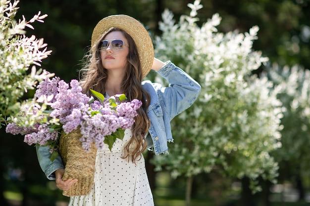 Dziewczyna z długimi włosami i słomianym kapeluszem. dziewczyna trzyma w rękach wiklinowy kosz z kwiatami. kosz z bzami. dziewczyna i kwiaty. spacer z koszem bzu w rękach. florystyka.