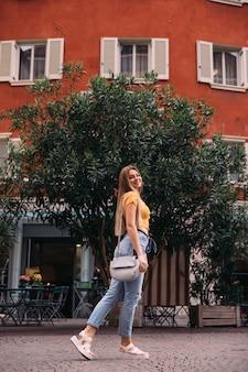 Dziewczyna z długimi włosami idzie ulicą miasta i patrzy w kamerę. stylowe ubrania i torebka.