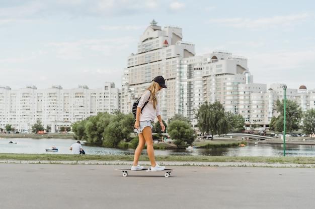 Dziewczyna z długimi włosami łyżwy na deskorolce. ulica, aktywny sport