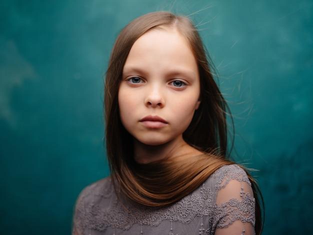 Dziewczyna z długimi włosami pozuje przycięty widok zielonego tła