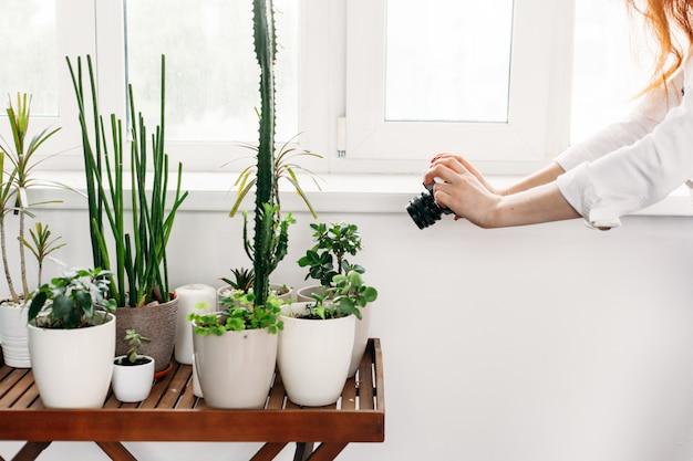 Dziewczyna z długimi włosami robi zdjęcia kwiatów w domu