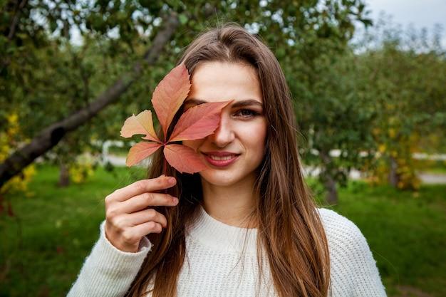 Dziewczyna z długimi włosami w białym swetrze trzyma przy twarzy czerwony jesienny liść dzikich winogron. dziewczyny w parku na tle dzikich winogron