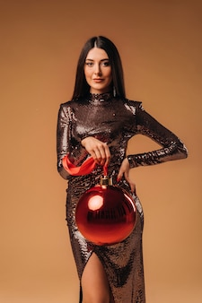Dziewczyna z długimi włosami w błyszczącej sukience z dużą bombką na brązowym tle.
