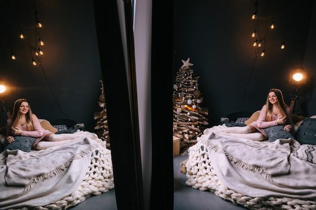Dziewczyna z długimi włosami w ciepłym swetrze na łóżku w sali weselnej przy choince
