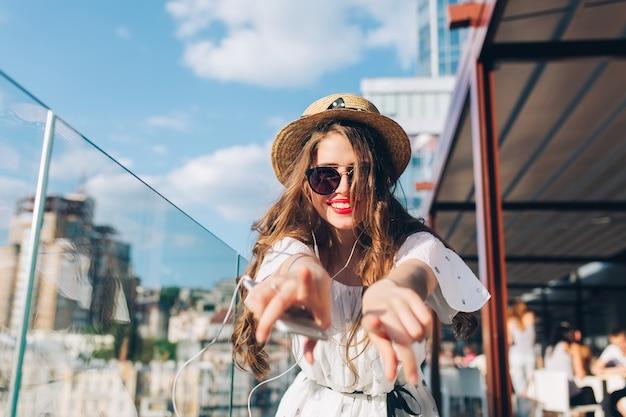 Dziewczyna z długimi włosami w okularach przeciwsłonecznych słucha muzyki w słuchawkach na balkonie. nosi białą sukienkę, czerwoną szminkę i kapelusz. wyciąga ręce do kamery. widok od tyłu.