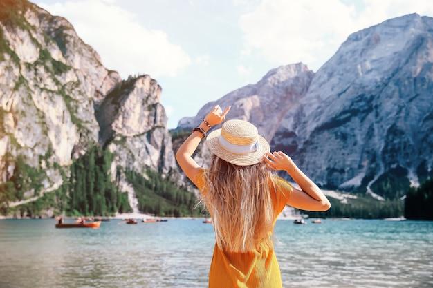 Dziewczyna z długimi włosami w sukience i kapelusiku nad jeziorem lago di braies w dolomitach. niesamowita podróż.