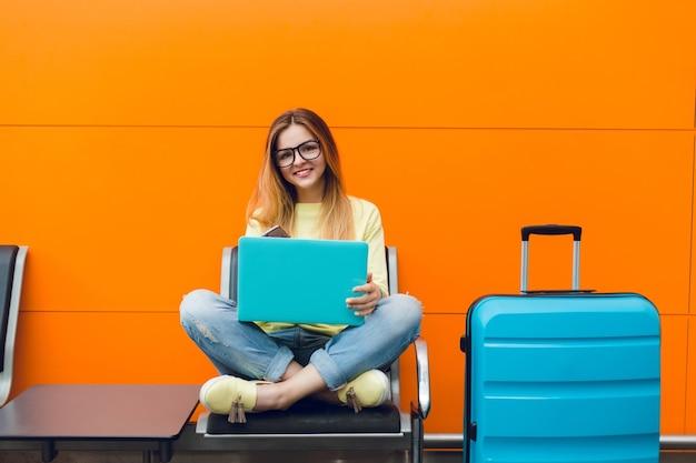 Dziewczyna z długimi włosami w żółtym swetrze siedzi na pomarańczowym tle. ma niebieską walizkę i laptopa. uśmiecha się szczęśliwa.