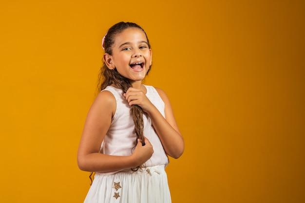 Dziewczyna z długimi zdrowymi włosami falowanymi. piękno, wygląd, fryzura. model dziecka z uśmiechem na ślicznej twarzy na żółtym tle. szczęśliwe dziecko, koncepcja dzieciństwa. młodzież, opieka i zdrowie.