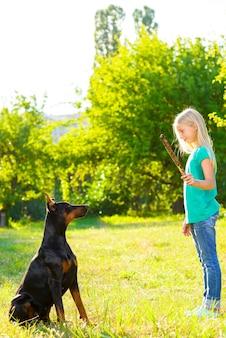 Dziewczyna z dobermannem w lato parku.