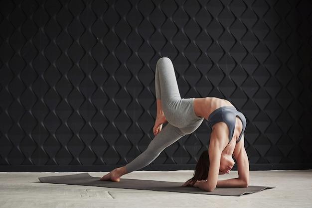 Dziewczyna z dobrą sylwetką fitness ma ćwiczenia w przestronnym pokoju