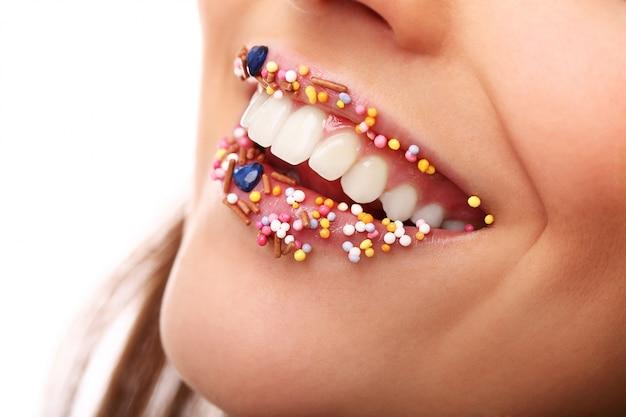 Dziewczyna z dodatkami cukierki na ustach. słodkie cukrowe usta