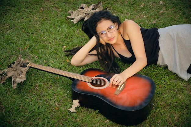 Dziewczyna z dredami odpoczywa na zielonej łące i opierając rękę na gitarze. 3
