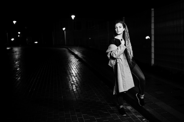 Dziewczyna z dredami spaceru w nocy ulica miasta.