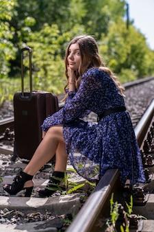 Dziewczyna z dużą podróżną walizką usiadła na szynach ułożonych w gęstym zielonym lesie. podróżować samemu