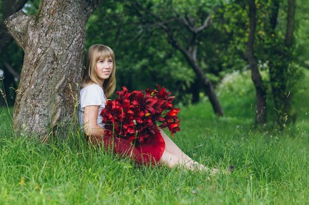 Dziewczyna z dużym bukietem fioletowych lilii