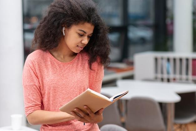 Dziewczyna z dużym kątem skoncentrowana na czytaniu