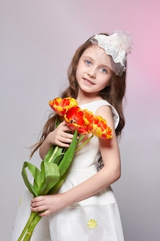 Dziewczyna z dużymi niebieskimi oczami z anime i bukietem kwiatów tulipanów w dłoniach. światowy dzień matki, dzień wiosny, bukiet wiosenny w rękach dziecka. długie kręcone blond włosy