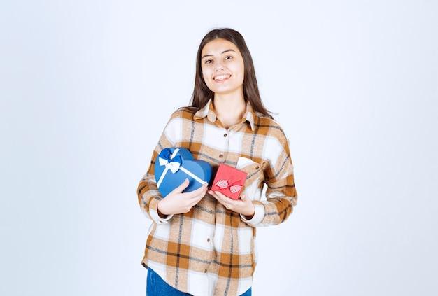 Dziewczyna z dwoma prezentami stojąc na białej ścianie.