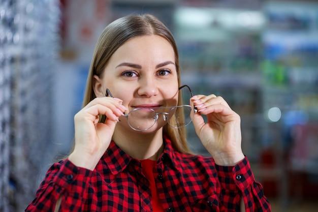 Dziewczyna z dysfunkcją wzroku wybiera okulary. ma na sobie koszulę i piękny uśmiech.