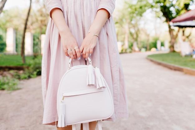 Dziewczyna z eleganckim manicure pozowanie podczas spędzania czasu na świeżym powietrzu, stojąc na alei w parku