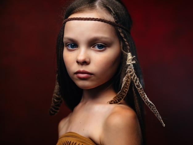 Dziewczyna z etniczną fryzurą rdzennych amerykańskich apaczów na czerwonym tle