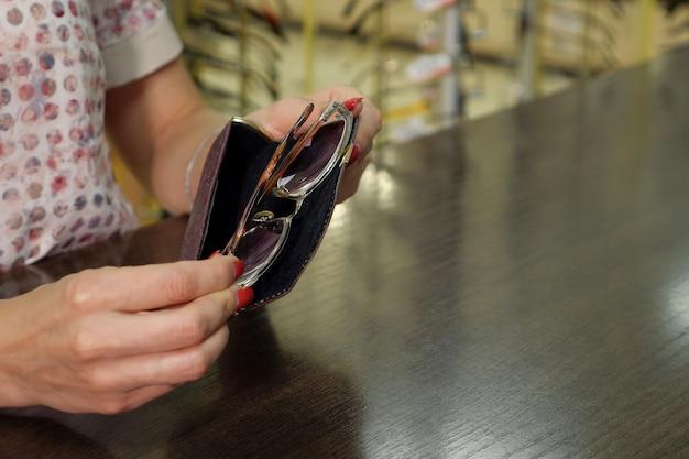 Dziewczyna z etui na okulary w rękach w sklepie optycznym, kopia przestrzeń