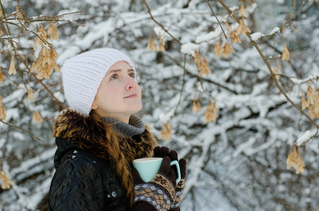 Dziewczyna z filiżanką herbaty na zewnątrz wśród drzew, patrząc w górę
